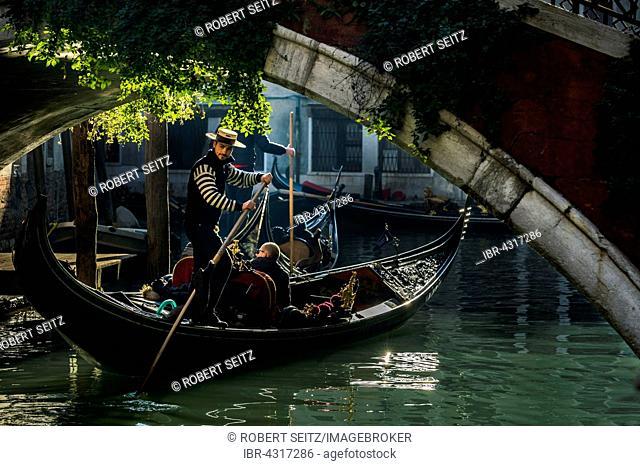 Small canal, gondola with gondolier travels under a bridge, Venice, Veneto, Italy