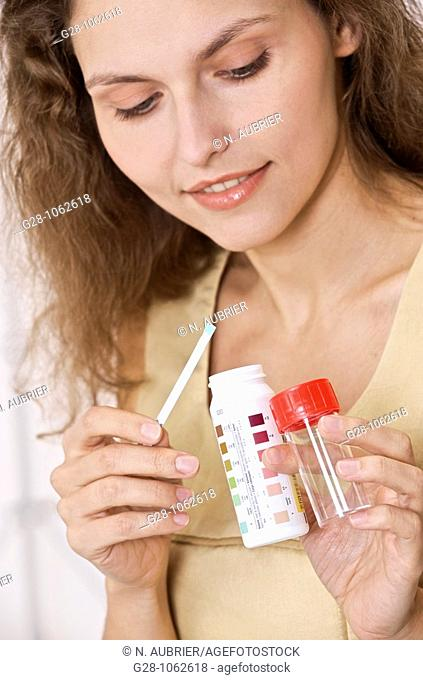 young smiling woman holding urine test tube for analysis, self analysis for diabetes