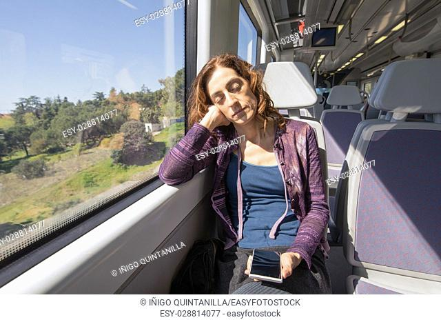 red hair woman dressed in purple and blue, sitting traveling by train, sleeping next to window glass, with mobile phone in hands