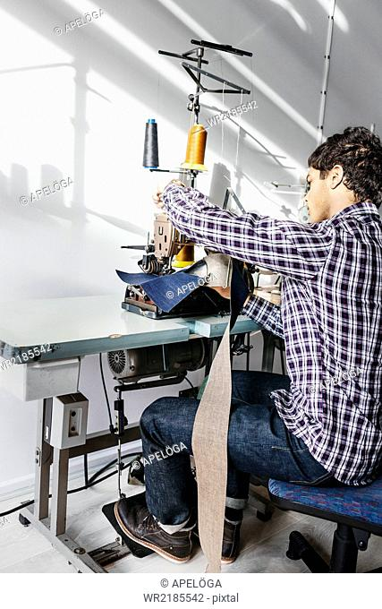 Full length of tailor sewing jeans in factory
