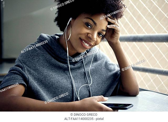 Young woman using smartphone and earphones, smiling, portrait