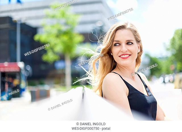 Portrait of smiling young woman sitting on a bench watching something