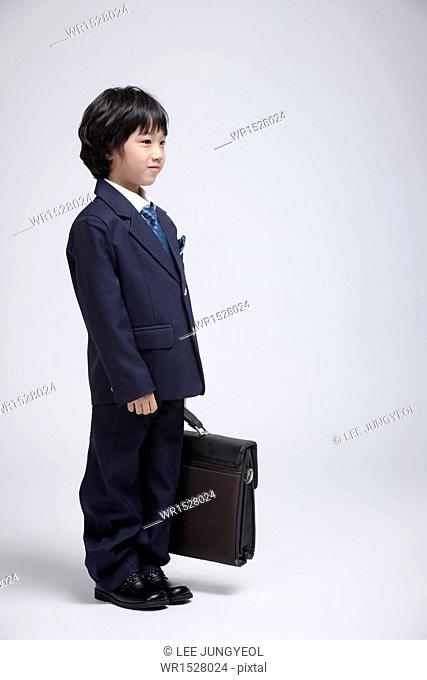 a boy in a business suit holding a suitcase