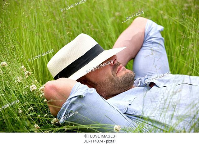 Serene man wearing fedora sleeping in tall summer grass