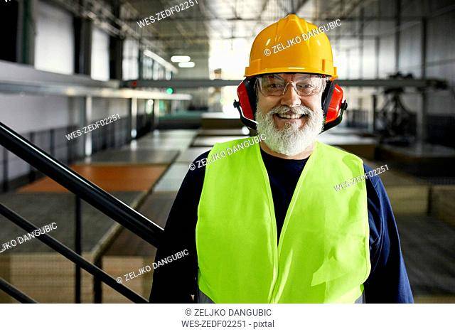 Portrait of smiling mature worker in factory warehouse