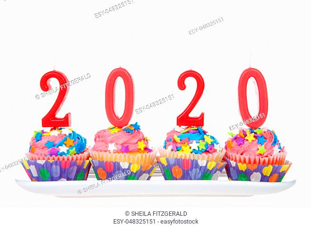 White cupcakes with rainbow colored frosting and brightly colored star candies on a rectangular plate with 2020 candles isolated on white background