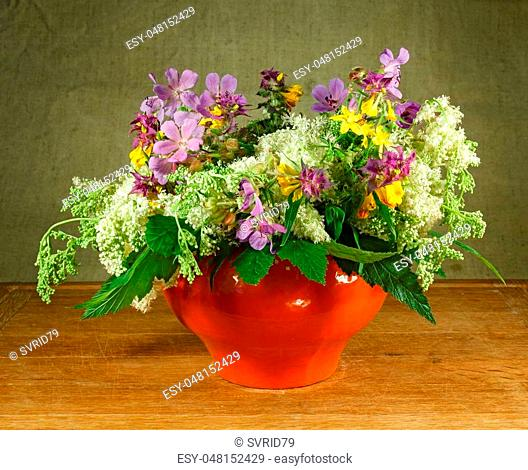 Still life. Bouquet of meadow flowers in orange pots standing on a wooden table. Rustic style. Meadow geranium, meadowsweet, hypericum perforatum