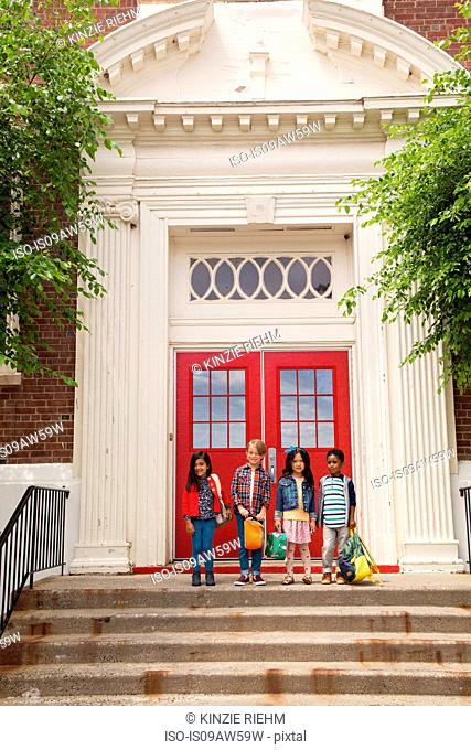 Portrait of four boys and girls standing elementary school entrance