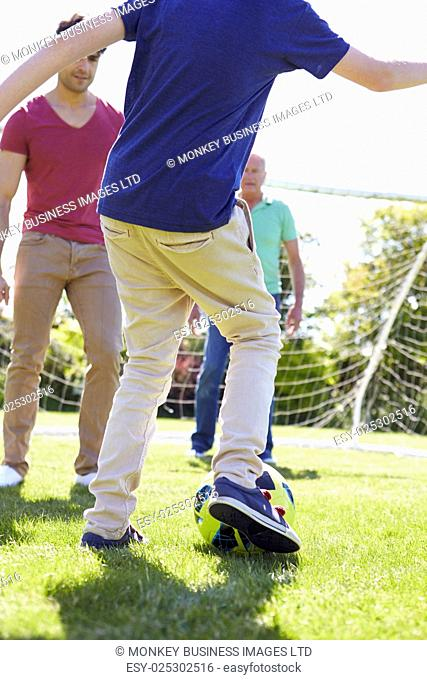 Male Three Generation Family Playing Football Together