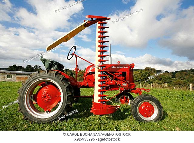 A restored antique 1952 International Farmall Cub Tractor with a mower  Note: the owner has supplied a property release for this tractor  However