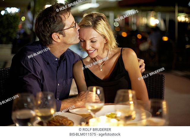 Caucasian husband kissing wife in restaurant