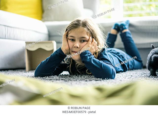 Portrait of girl lying with hare in living room