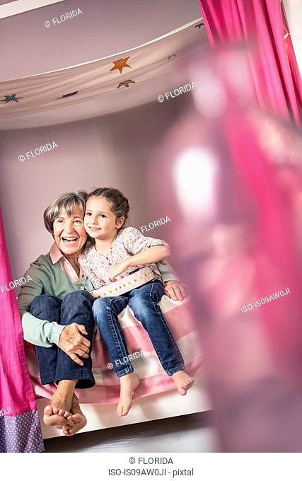 Girl and grandmother sitting on bed