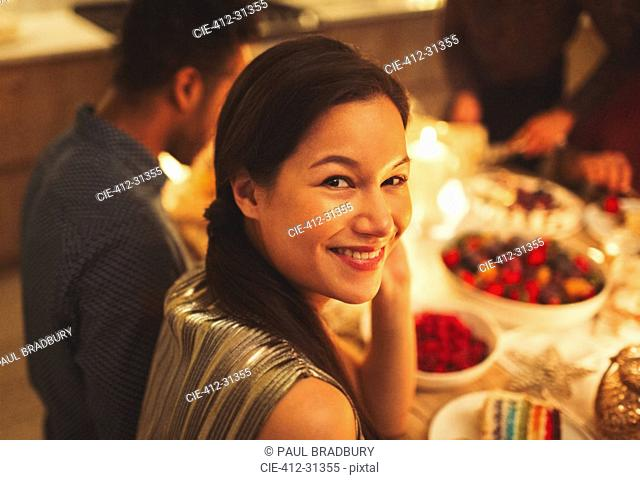 Portrait smiling woman at candlelight dinner party
