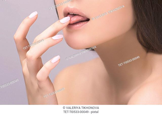 Young woman licking her finger
