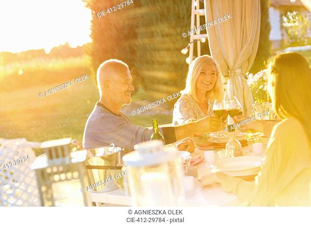Senior couple an adult daughter toasting wine glasses at sunny patio table