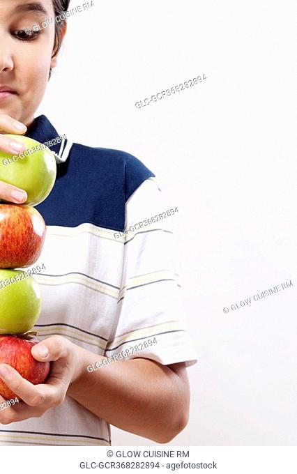 Close-up of a boy holding apples