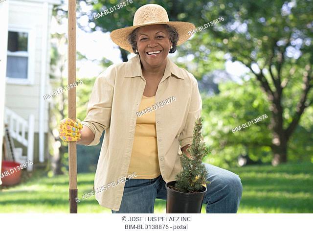 Older African American woman planting tree in backyard