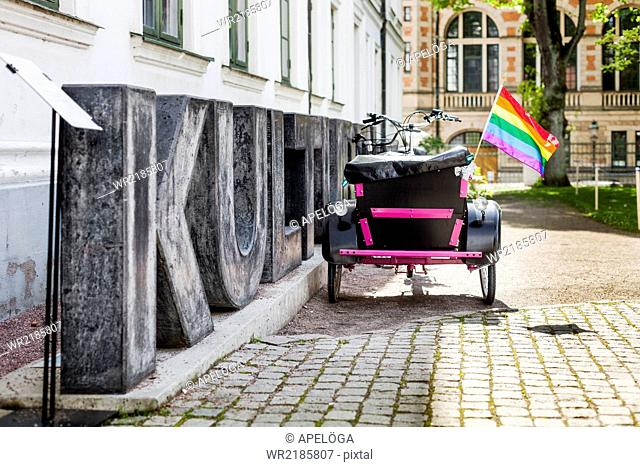 Rainbow flag on tricycle cart by sign