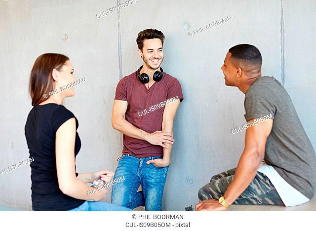 Young female and male students chatting together at higher education college