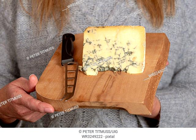 Woman holding Cheese board with a knife and piece of blue cheese