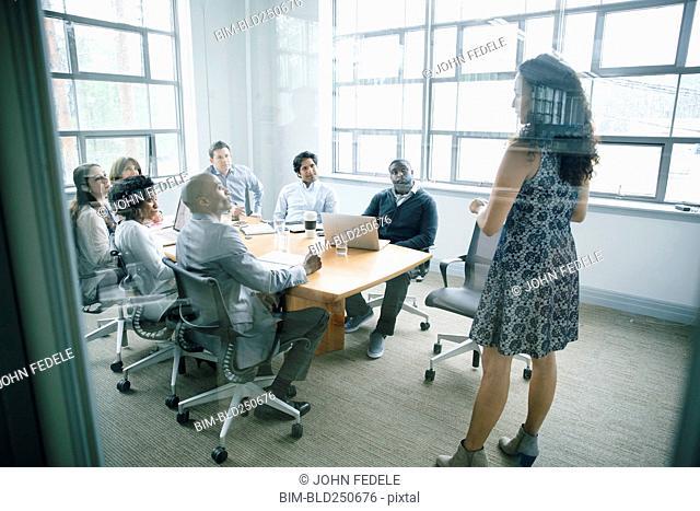 Businesswoman talking behind window in meeting