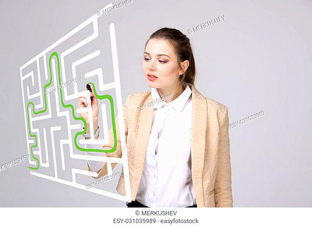 Young businesswoman finding the maze solution writing on whiteboard