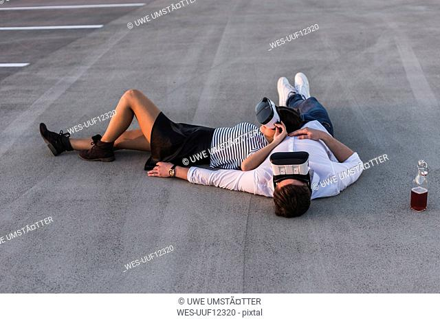 Young couple lying on parking level wearing VR glasses