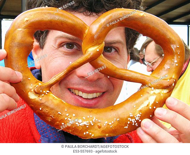 Man, early 40s, holding large pretzel, Kloster Andechs beer garden, near Munich, Germany