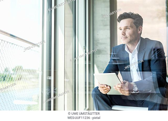 Portrait of businessman with tablet looking through window
