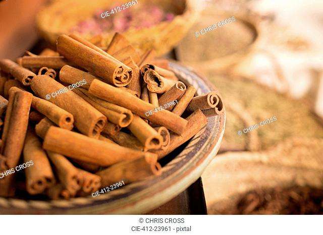 Cinnamon sticks on plate and other spices in background in spice market