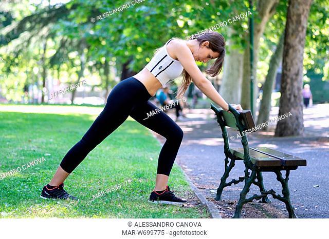Ragazza che fà stretching in un parco pubblico