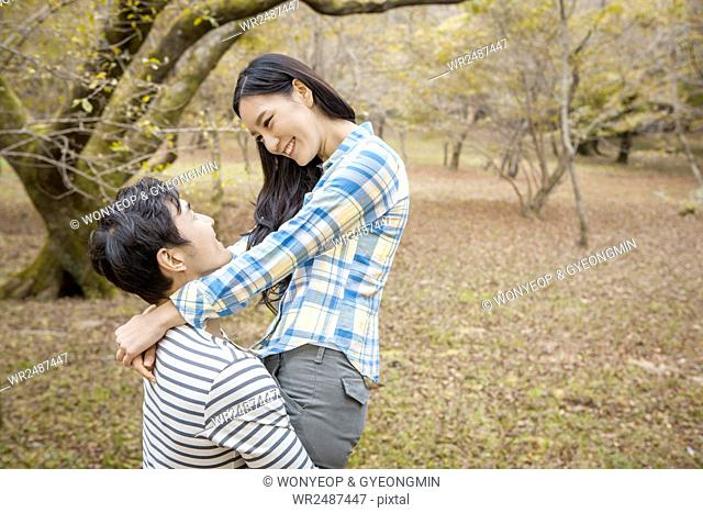 Side view portrait of young smiling couple hugging face to face in park