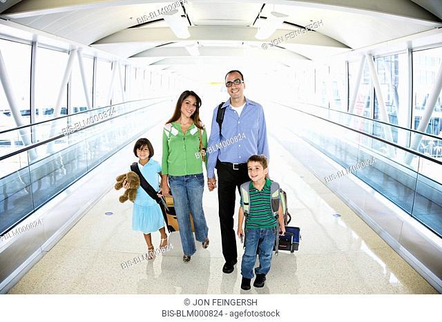 Hispanic family walking in airport