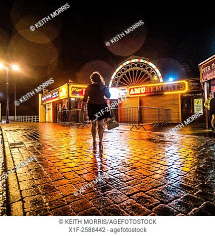 Rear view of a young woman outside a night club disco on new yeart's eve in the rain UK