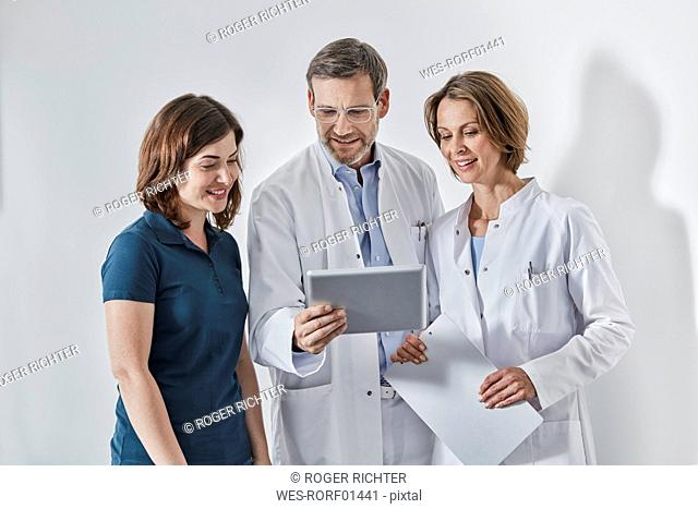 Doctors and medical secretary using tablet