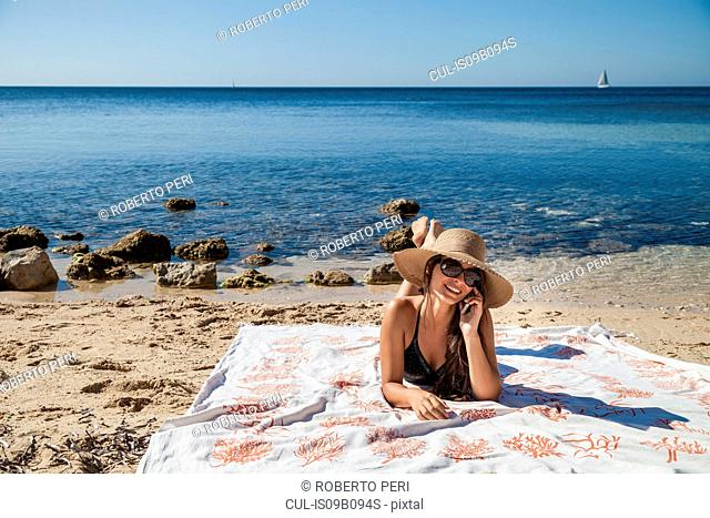 Young woman chatting on smartphone whilst sunbathing on beach, Villasimius, Sardinia, Italy