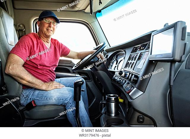 Caucasian man truck driver in the cab of his commercial truck