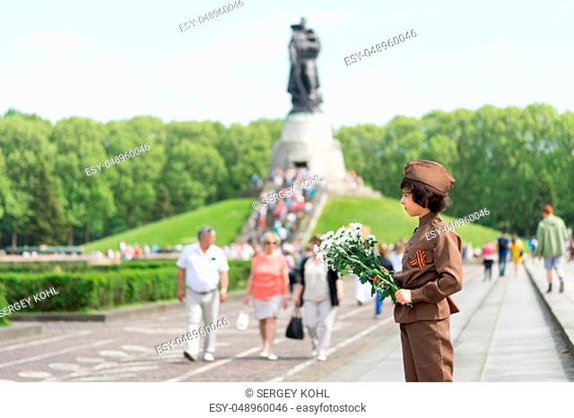 Portrait of a boy with flowers, in the uniform of a soldier of the Red Army during the Second World War. Soviet War Memorial (Treptower Park), Berlin, Germany