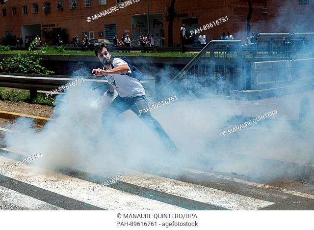 A protestor throws back a cartridge of tear gas to the police forces during a demonstration against the government in Caracas, Venezuela, 4 April 2017