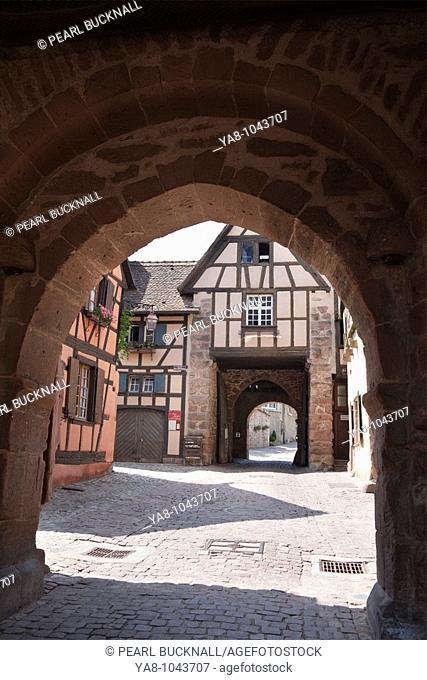 Rue de General de Gaulle, Riquewihr, Alsace, Haut-Rhin, France, Europe  View through Dolder tower arch to town walls gateway in medieval commune on the Alsarian...