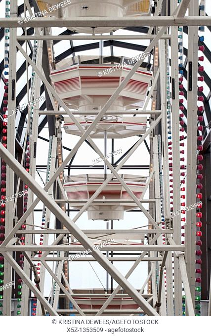A Ferris Wheel's carriages rising up to the light