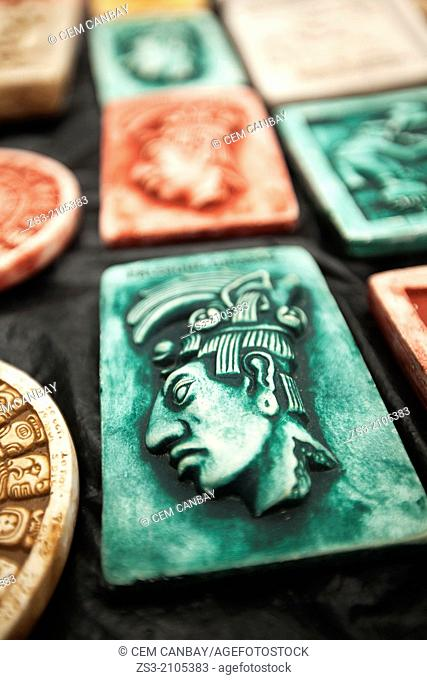 Stone tablets with figure of Kan Balam II, the ruler of Palenque as colorful mexican souvenirs, at a street shop in Palenque, Chiapas Region, Mexico
