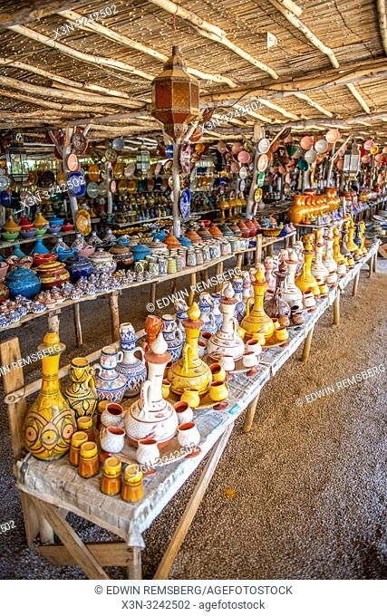 Endless tables of organized, colorful, pottery for sale at outdoor market, Tangier, Morocco