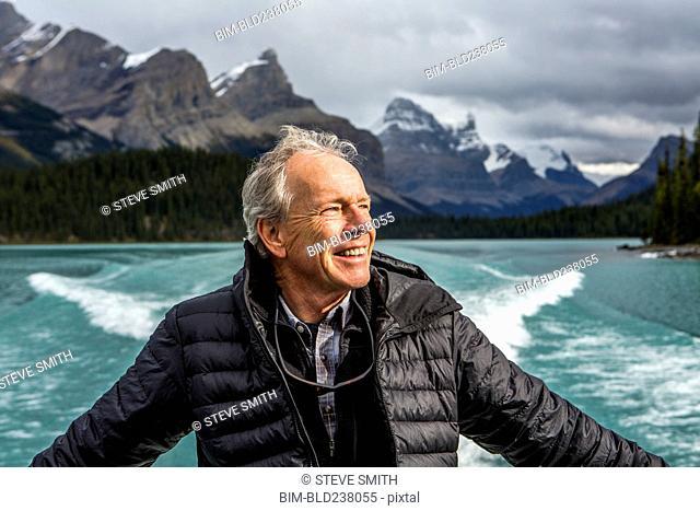 Caucasian man on boat in mountain lake