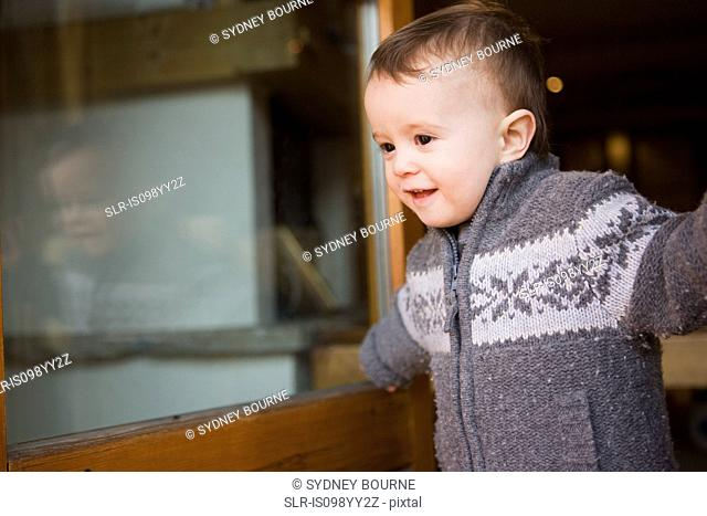Young boy in chalet doorway