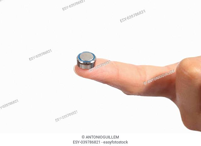 Woman hand holding a button battery with the forefinger isolated on a white background