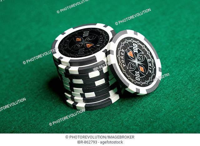 Poker chips, black, stacked on green felt