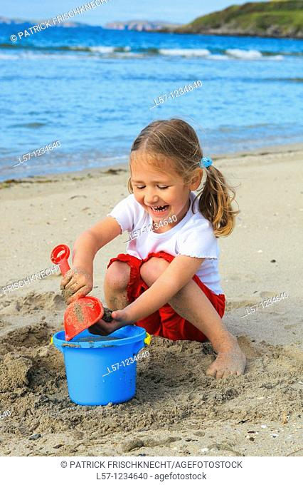girl playing on sandy beach, Sutherland, Scotland