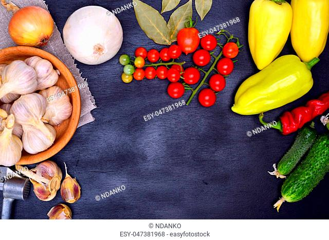 Fresh vegetables: tomatoes, cucumbers and garlic on a black background, empty space in the middle